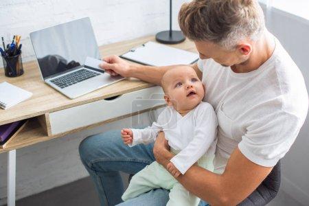 Foto de Padre sentado en el escritorio de la computadora con tarjeta de crédito para compras en línea y explotación adorable hijita en casa - Imagen libre de derechos