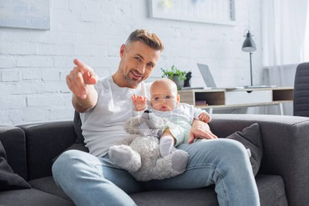 smiling father sitting on couch with baby daughter and pointing with finger at something