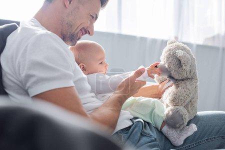 Photo pour Mise au point sélective de l'adorable petite fille jouant avec ours en peluche et assis sur le canapé avec le père à la maison - image libre de droit