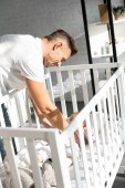 happy dad putting infant daughter into baby crib at home