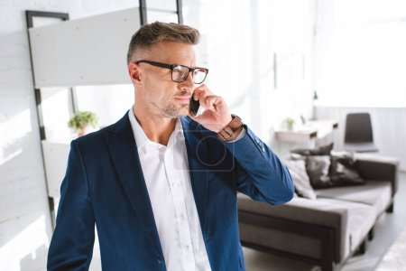 Photo for Handsome businessman in glasses talking on smartphone in living room - Royalty Free Image