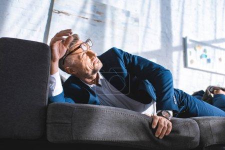 Foto de Empresario borracho en gafas acostado en el sofá con sol en la sala de estar - Imagen libre de derechos