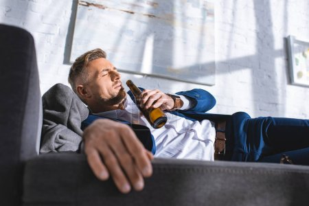 Photo for Drunk businessman lying on sofa with closed eyes and drinking alcohol from bottle - Royalty Free Image