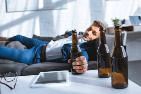 Photo for Selective focus of bottle in hand of drunk businessman lying on sofa - Royalty Free Image