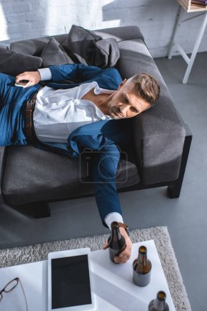 drunk businessman holding bottle and lying on sofa in living room