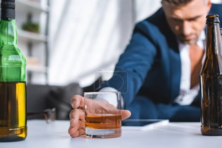selective focus of glass with whiskey in hand of drunk businessman