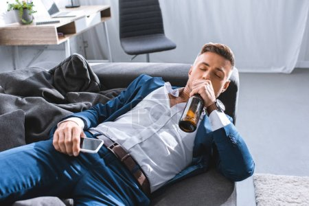Photo for Depressed businessman drinking alcohol from bottle and lying on sofa in living room - Royalty Free Image