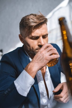 selective focus of businessman holding glass and drinking whiskey