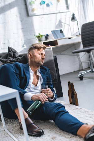 Photo for Drunk businessman sitting on carpet with closed eyes - Royalty Free Image