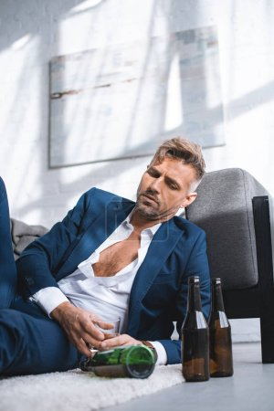 depressed and drunk businessman holding glass with alcohol drink in living room