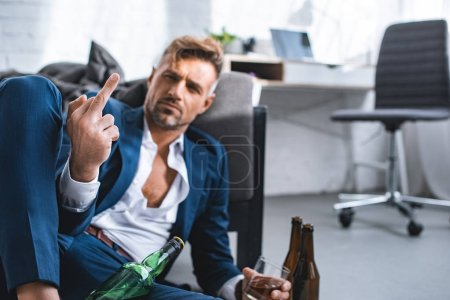 Photo for Selective focus of middle finger of drunk businessman in living room - Royalty Free Image