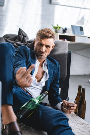 Photo for Drunk businessman showing middle finger and holding glass with alcohol drink - Royalty Free Image
