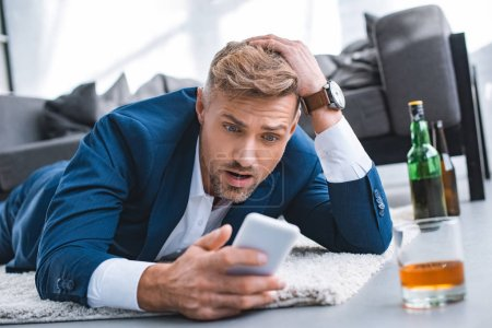 shocked businessman looking at smartphone and lying on carpet near glass with alcohol drink