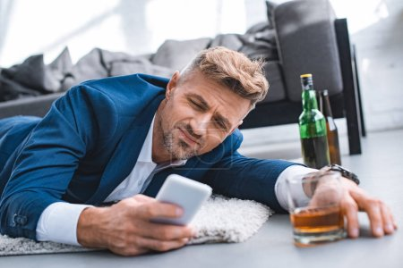 Photo for Selective focus of drunk businessman lying on carpet and using smartphone - Royalty Free Image