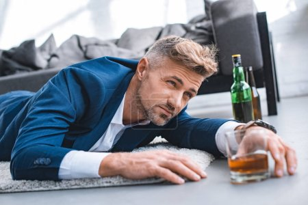 Photo for Selective focus of drunk businessman lying on carpet near glass with alcohol drink - Royalty Free Image
