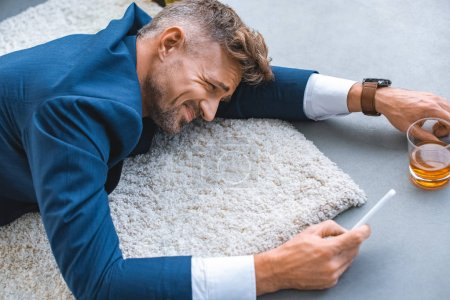 Photo for Drunk businessman lying on carpet with smartphone in hand - Royalty Free Image