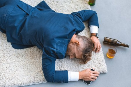 Photo for Top view of drunk businessman lying on carpet with smartphone in hand - Royalty Free Image