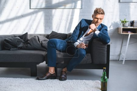 pensive businessman sitting on sofa and holding glass with alcohol drink