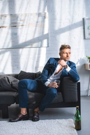 Photo for Businessman sitting on sofa and holding glass with alcohol drink - Royalty Free Image