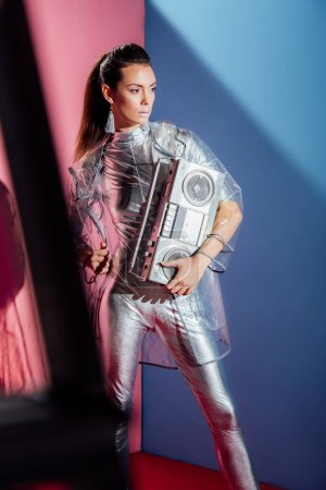 fashionable young woman in metallic bodysuit and raincoat posing with retro boombox on pink and blue background