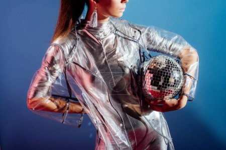cropped view of model in metallic bodysuit and raincoat posing with disco ball on blue background