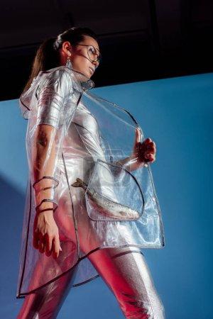 Photo pour Vue de dessous de jolie fille en body argenté et imperméable posant avec poisson sur fond bleu - image libre de droit