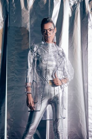 Photo for Attractive young model posing in silver bodysuit and raincoat on metallic background - Royalty Free Image