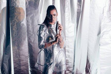 Foto de Moda joven modelo en plata mono y capa impermeable con peces sobre fondo metálico - Imagen libre de derechos
