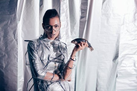 Photo for Attractive young model in silver bodysuit and raincoat holding fish on metallic background - Royalty Free Image