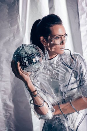 beautiful stylish young woman in silver bodysuit and raincoat posing with disco ball on metallic background