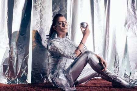 beautiful girl in fashionable silver bodysuit and raincoat holding silver apple on metallic background