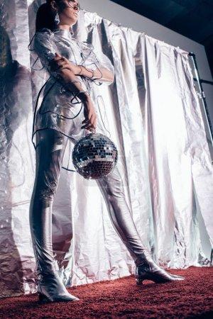 Photo pour Vue de dessous d'une fille à la mode en argent Body et imperméable posant avec boule disco sur fond métallique - image libre de droit