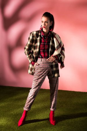 fashionable model posing in checkered suit on pink background