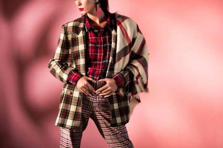Photo pour Vue recadrée de fille posant en costume à carreaux chaud sur fond rose - image libre de droit