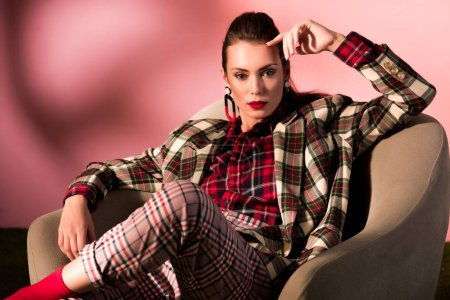 fashionable woman in checkered suit posing in armchair on pink background