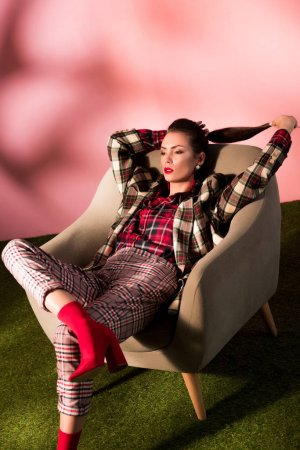 Photo for Beautiful stylish woman in checkered suit posing in armchair on pink background - Royalty Free Image