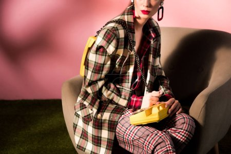 Photo for Cropped view of girl in checkered suit posing in armchair with vintage telephone on pink background - Royalty Free Image