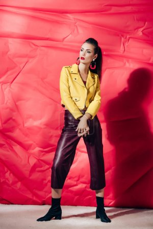 Photo for Stylish brunette model posing in yellow leather jacket on red background - Royalty Free Image