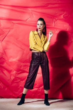 Foto de Moda modelo morena posando en chaqueta de cuero amarilla sobre fondo rojo - Imagen libre de derechos