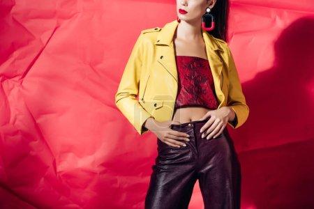 Foto de Recortar vista de elegante mujer posando en chaqueta de cuero amarilla sobre fondo rojo - Imagen libre de derechos