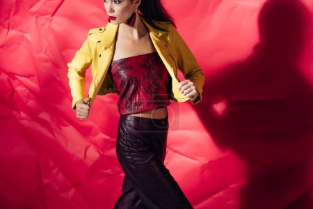 attractive elegant woman posing in yellow leather jacket on red background