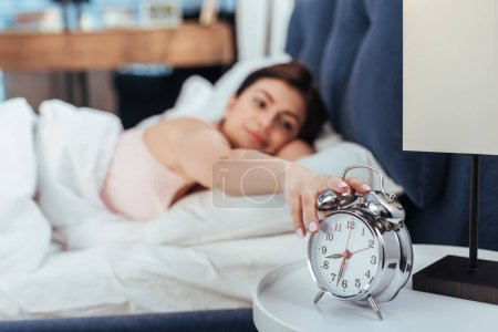 selective focus of young woman turning off alarm clock in bedroom during morning time at home