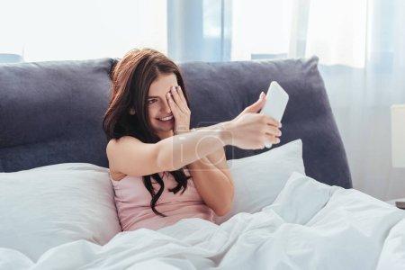 Photo pour Fille souriante prenant selfie sur smartphone tout en étant assis sur le lit pendant la matinée à la maison - image libre de droit