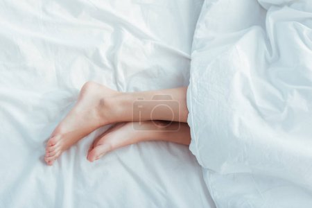 low section of female legs under blanket in bed