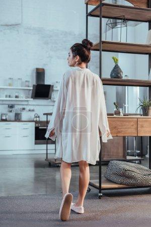 Photo pour Vue arrière de la fille attrayante posant en chemise blanche pendant le matin à la maison - image libre de droit