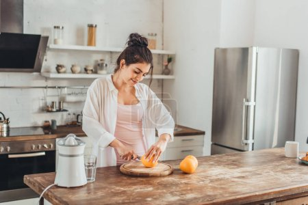 Photo for Smiling woman cutting orange by knife on wooden board in kitchen - Royalty Free Image