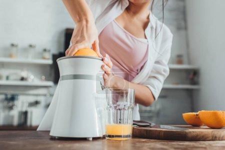 Photo pour Vue partielle de fille fabrication de jus d'orange frais avec le presse-agrumes à une table en bois dans la cuisine - image libre de droit
