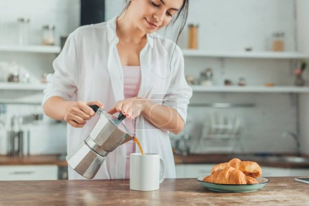 Photo for Pretty girl pouring coffee into cup at wooden table with croissants in kitchen at home - Royalty Free Image