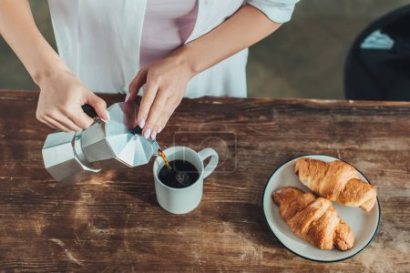 Photo for Cropped image of girl pouring coffee into cup at wooden table with croissants in kitchen at home - Royalty Free Image