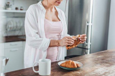 Photo pour Vue partielle de la femme prenant son petit déjeuner avec croissants et café à table en bois dans la cuisine à la maison - image libre de droit